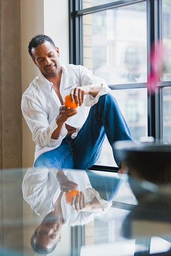 Man relaxing on window sill in loft apartment : Stock Photo