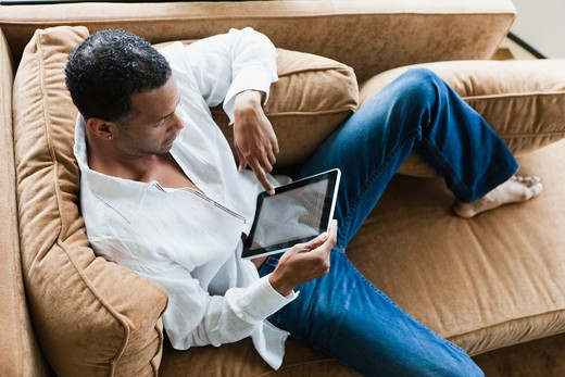 Man sitting on couch with ebook : Stock Photo