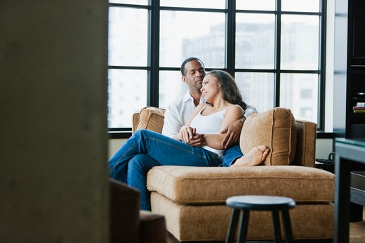 Stock Photo: 4064R-366 Couple relaxing on couch in loft apartment