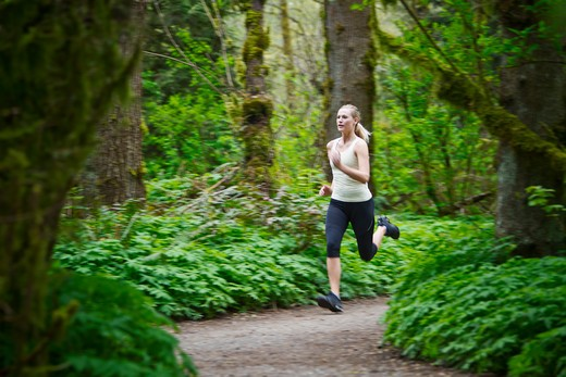 Stock Photo: 4064R-389 Portland, Oregon, USA, Woman trail running in forest