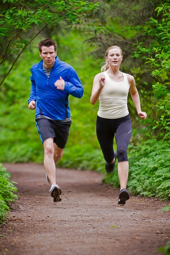 Portland, Oregon, USA, Couple running together on trail in forest : Stock Photo