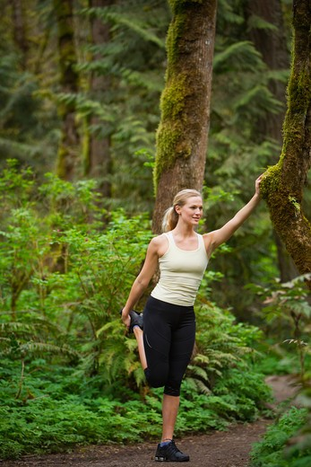 Stock Photo: 4064R-398 Portland, Oregon, USA, Woman stretching before run, on trail in forest