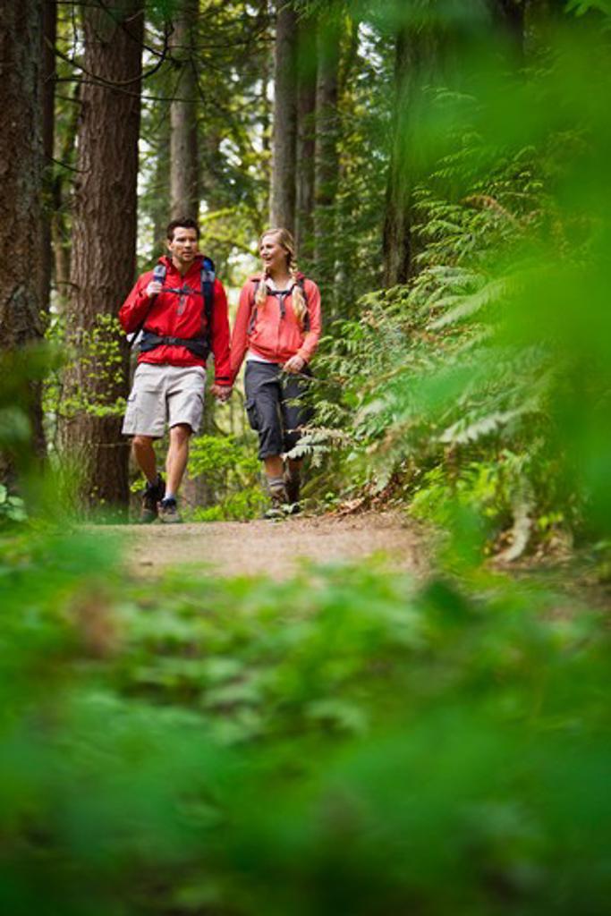 Stock Photo: 4064R-409 Portland, Oregon, USA, Couple walking on trail through forest