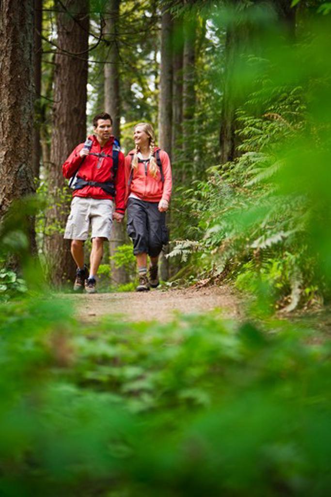 Portland, Oregon, USA, Couple walking on trail through forest : Stock Photo