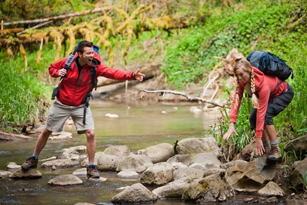 Portland, Oregon, USA, Man helping woman across creek : Stock Photo