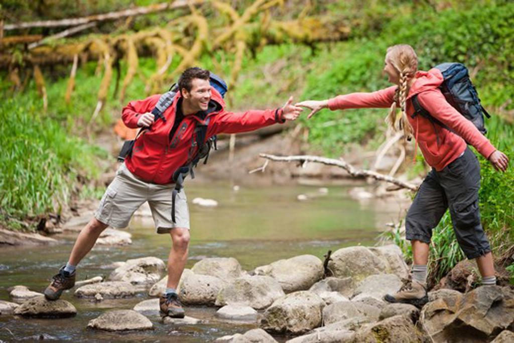 Stock Photo: 4064R-456 Portland, Oregon, USA, Man helping woman across creek