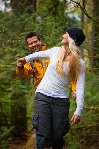 Portland, Oregon, USA, Couple walking along log in forest : Stock Photo