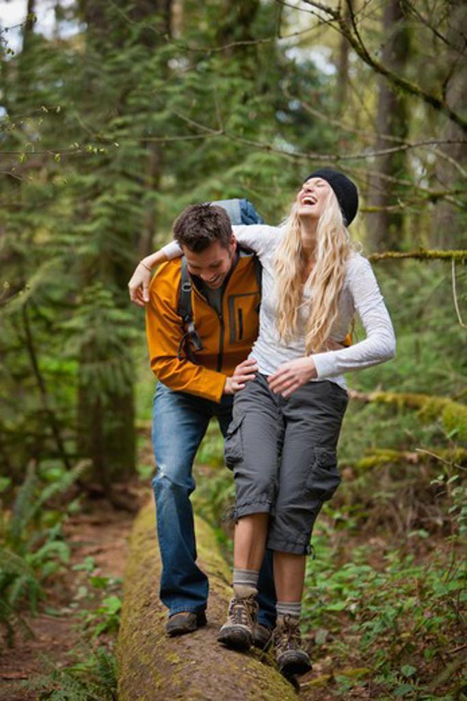 Portland, Oregon, USA, Couple walking along log in forest : Stock Photo