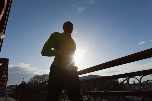 Man jogging, backlit by sun : Stock Photo
