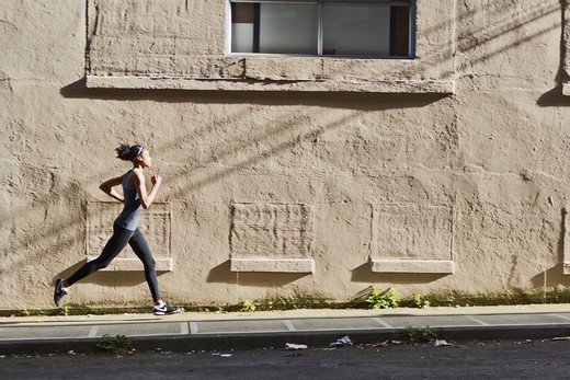 Stock Photo: 4064R-482 Woman jogging up street