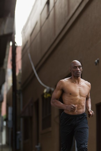 Stock Photo: 4064R-508 Shirtless man jogging in street