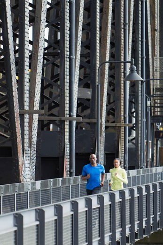 Man and woman running on bridge : Stock Photo
