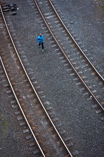 Man running across railroad tracks : Stock Photo