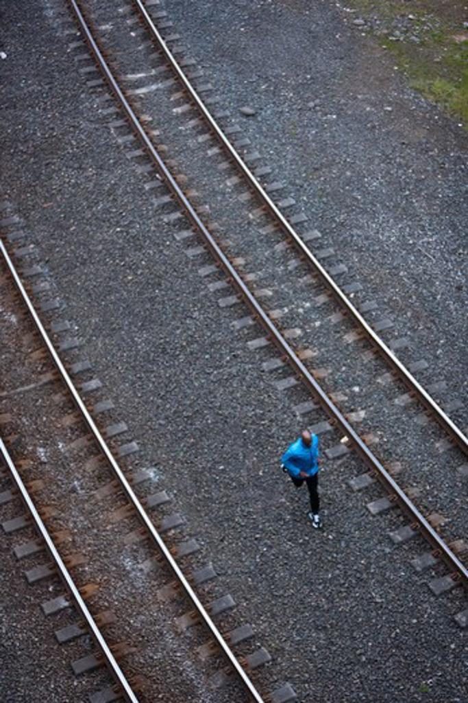 Man running across railroad tracks : Stock Photo