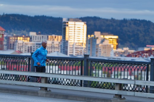 Man running along bridge : Stock Photo