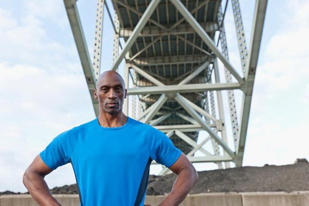 Stock Photo: 4064R-561 Male Athlete standing beneath bridge
