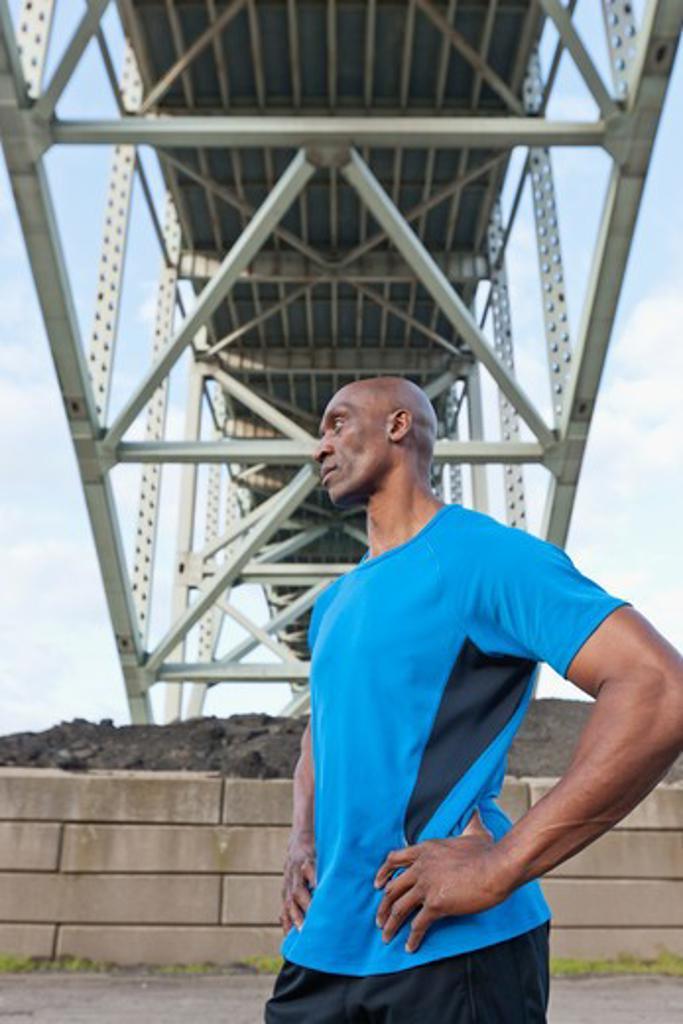 Male Athlete standing beneath bridge : Stock Photo