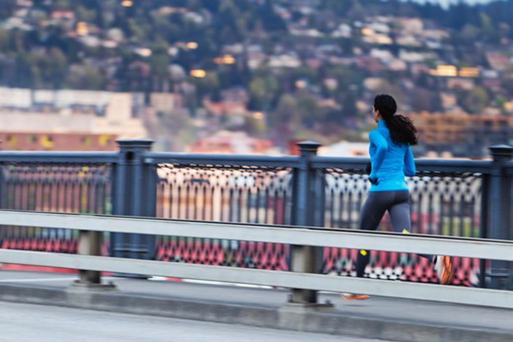 Stock Photo: 4064R-566 Young woman running along bridge