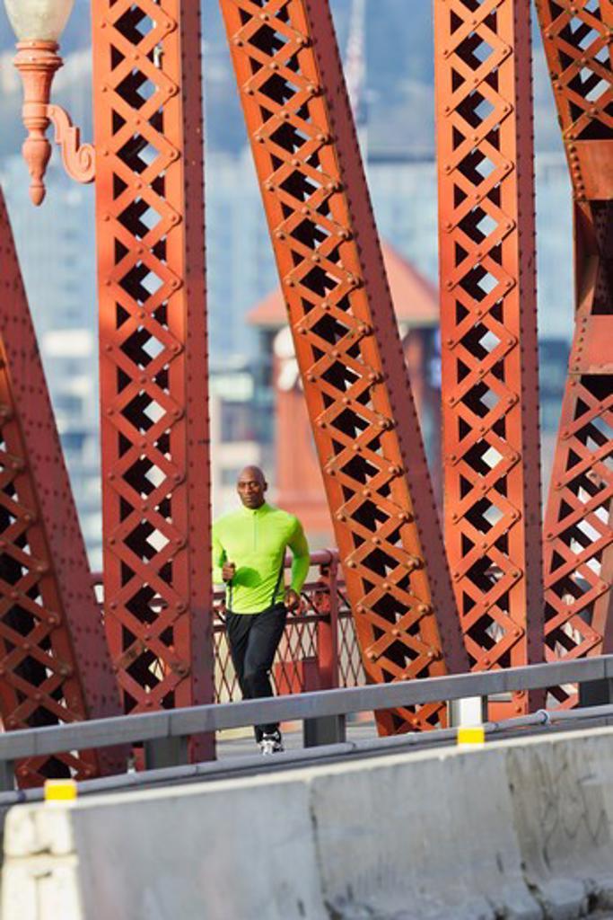 Man running along bridge : Stock Photo