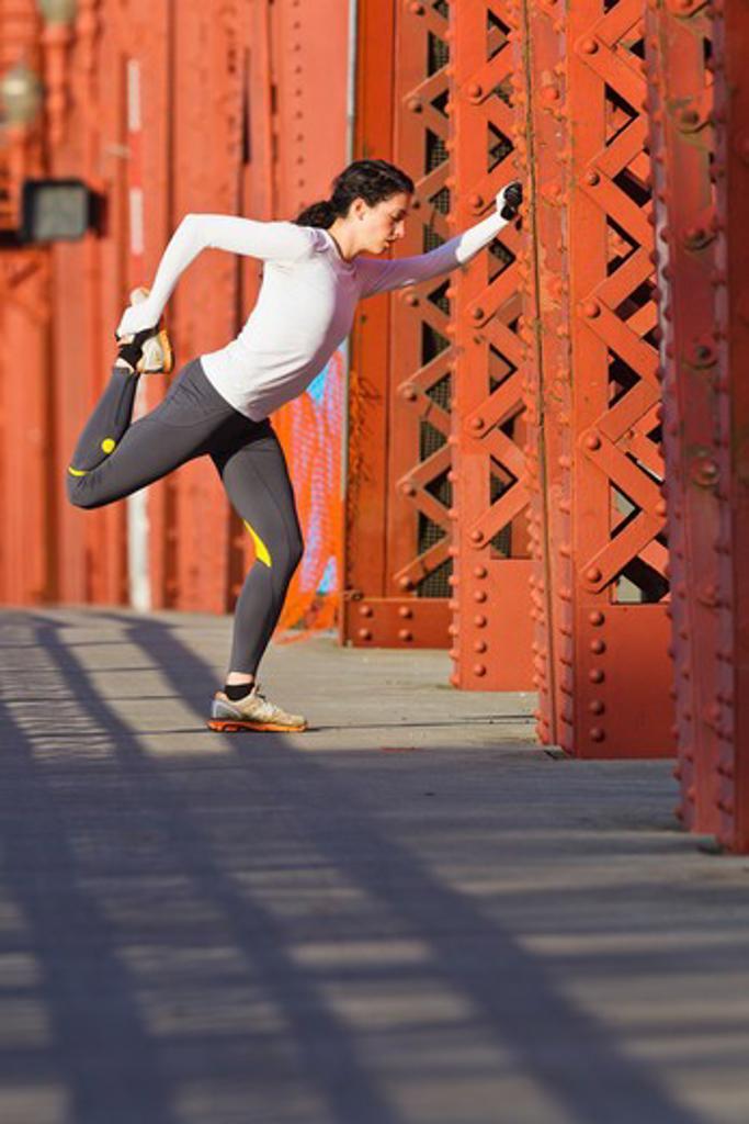 Stock Photo: 4064R-571 Female jogger, stretching on bridge