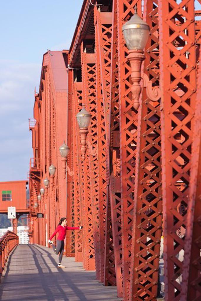 Stock Photo: 4064R-574 Female jogger, stretching on bridge
