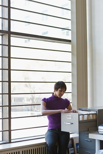 Stock Photo: 4064R-601 Businesswoman at filing cabinet in office