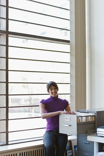 Portrait of businesswoman at filing cabinet in office : Stock Photo