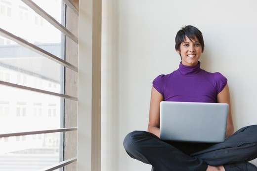 Portrait of businesswoman using laptop in office : Stock Photo