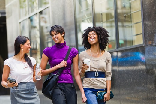 Three businesswomen walking outside office : Stock Photo
