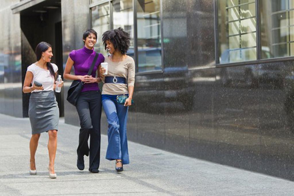 Three businesswomen walking outside office : Stock Photo