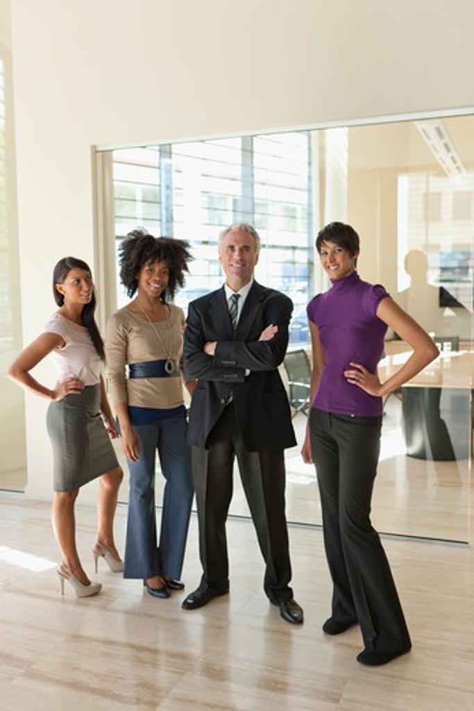 Portrait of three businesswomen with businessman in office : Stock Photo