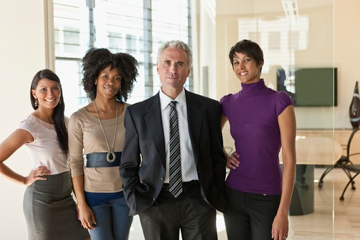 Portrait of three businesswomen with businessman in office : Stock Photo