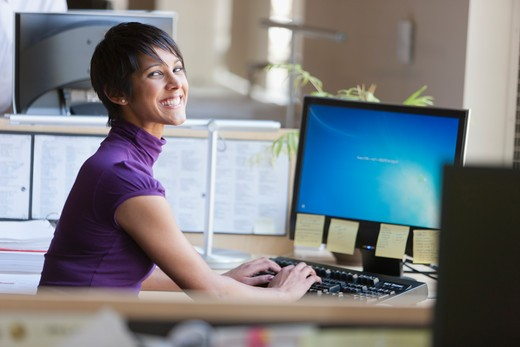 Portrait of businesswoman using computer at office desk : Stock Photo