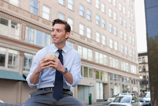 Businessman eating sandwich outside office building : Stock Photo