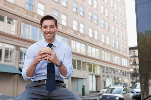 Stock Photo: 4064R-691 Businessman eating sandwich outside office building