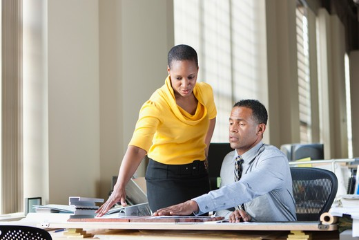 Stock Photo: 4064R-743 Man and woman consulting at desk in office