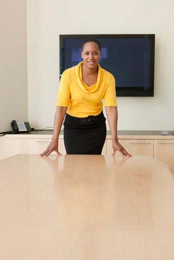 Businesswoman standing at conference table, portrait : Stock Photo