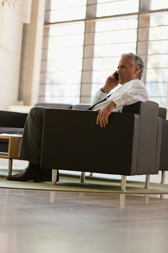 Businessman waiting in office lobby : Stock Photo