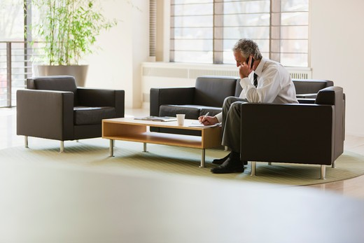 Business executive waiting in office lobby : Stock Photo