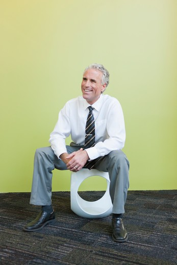 Mature businessman sitting on designer chair against yellow background, laughing : Stock Photo