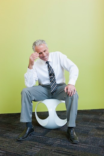 Stock Photo: 4064R-824 Mature businessman sitting on designer chair against yellow background