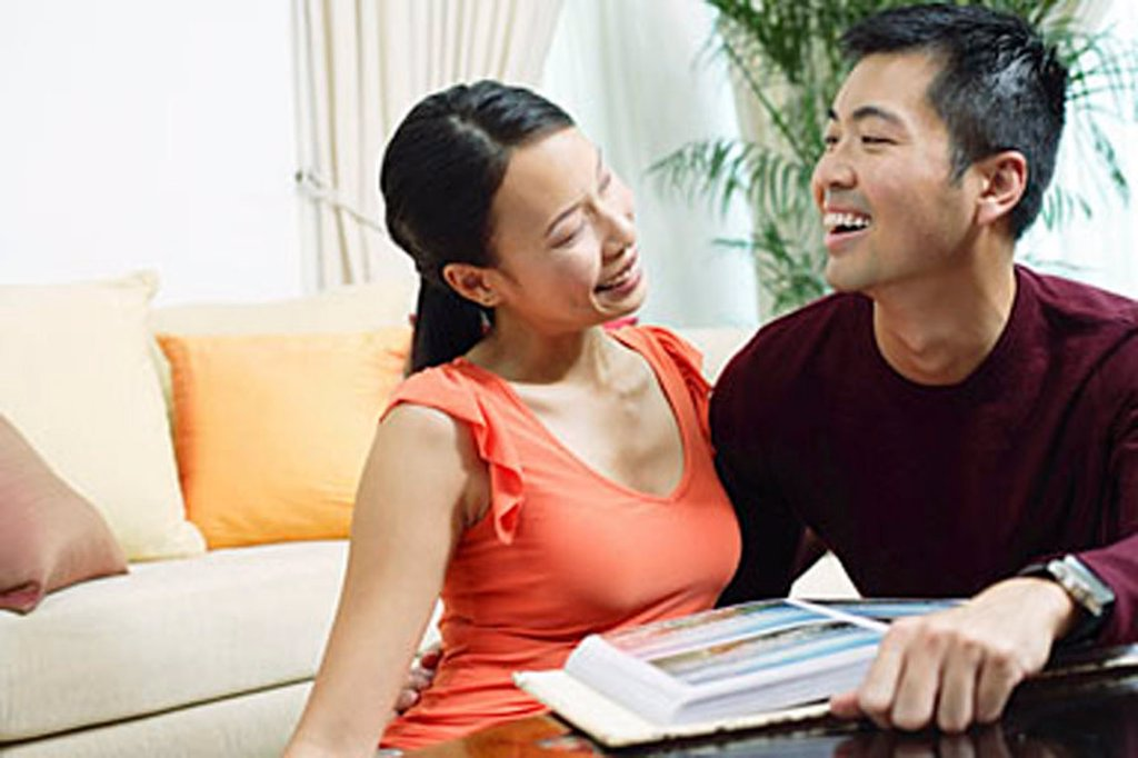 Stock Photo: 4065-10472 Couple at home, smiling at each other, photo album in front of them