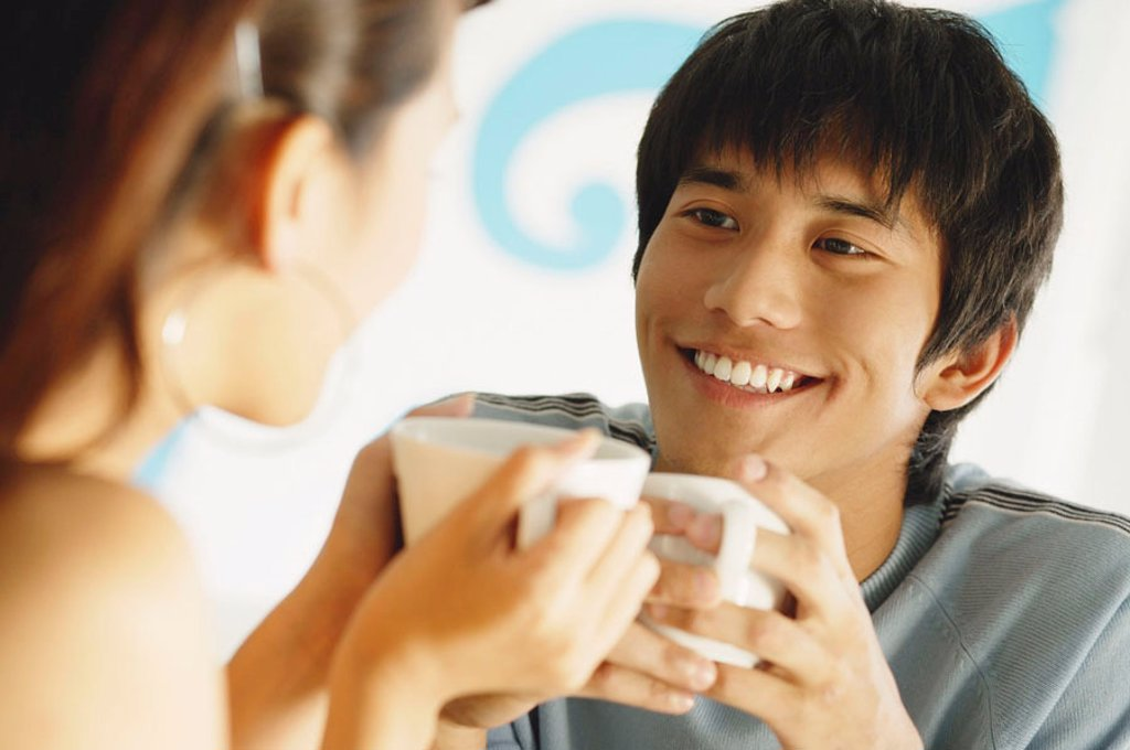 Couple having coffee, looking at each other : Stock Photo