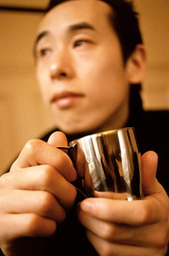 Man holding silver cup looking off camera. : Stock Photo