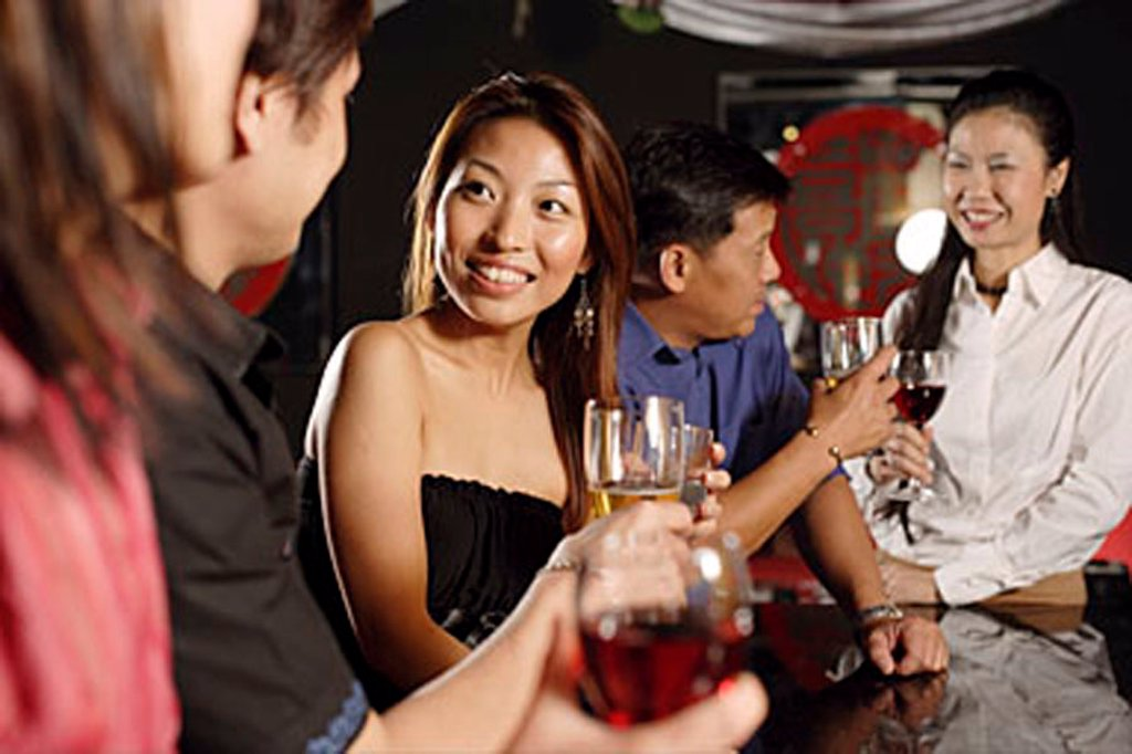 Men and women at bar, drinking : Stock Photo