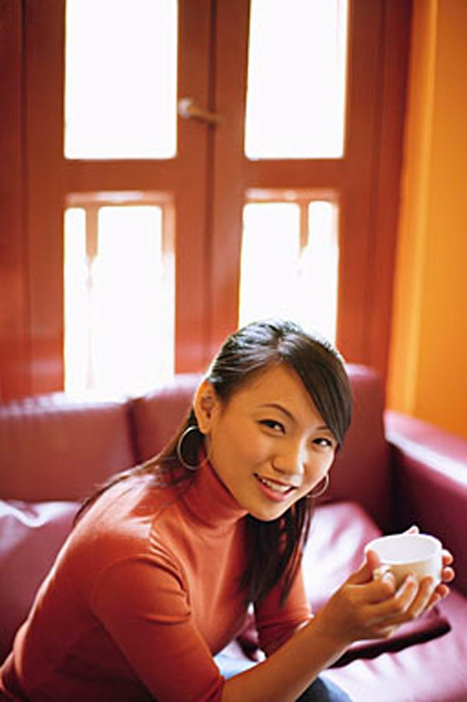 Young woman sitting, holding cup, smiling at camera : Stock Photo
