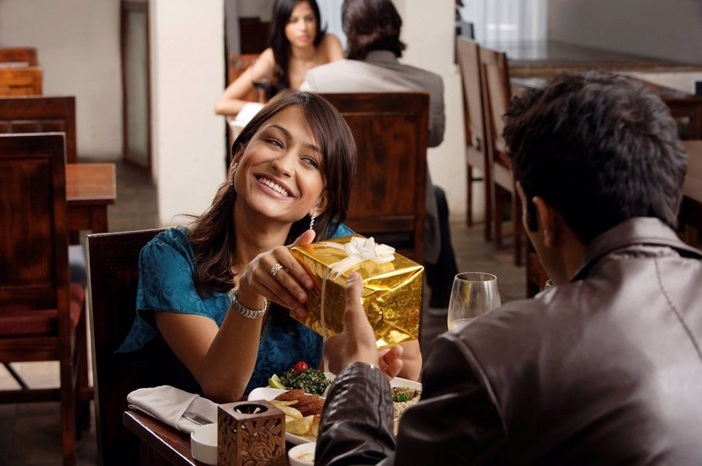 young man giving present to young woman : Stock Photo