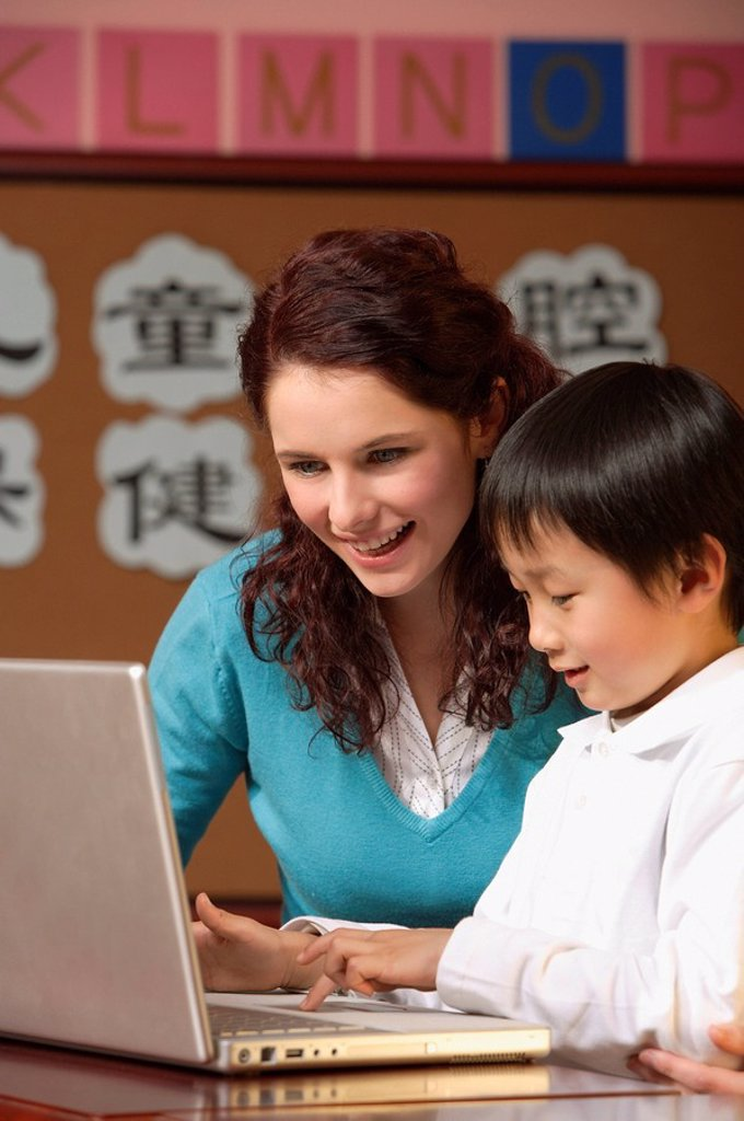 Stock Photo: 4065-11612 Teacher helping student use a laptop in class