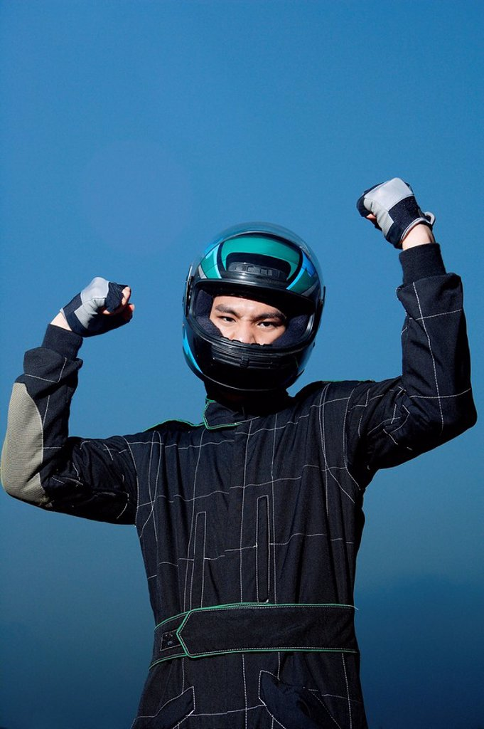 Race car driver in protective sportswear, raising fists : Stock Photo