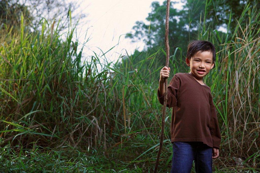 Boy holding stick. : Stock Photo